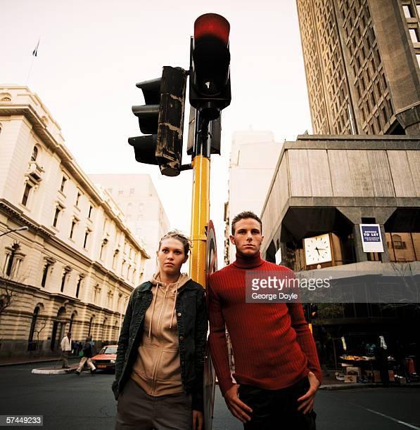 portrait of a couple leaning on a traffic light on a street - ongeduldig stockfoto's en -beelden