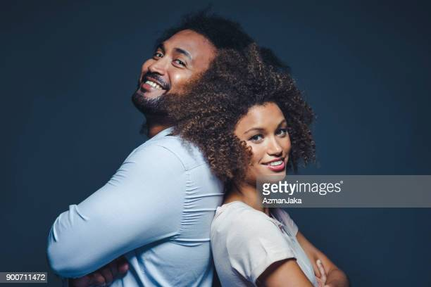 黒い背景に混血民族のカップルの肖像画 - 背中合わせ ストックフォトと画像
