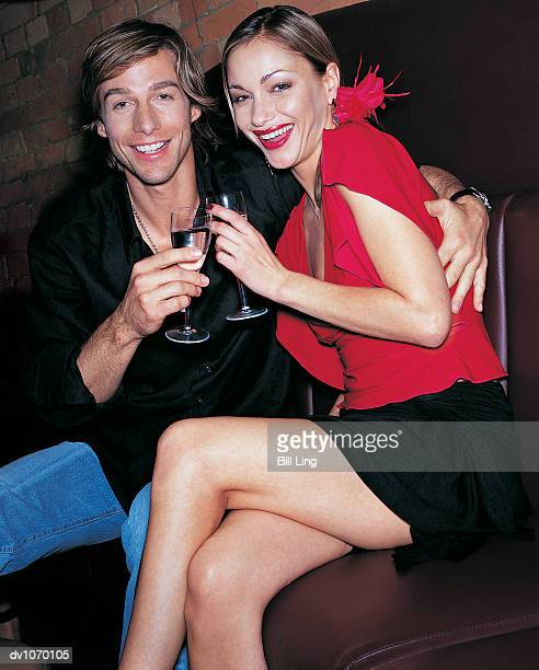 portrait of a couple sitting and holding champagne flutes - clubkleding stockfoto's en -beelden