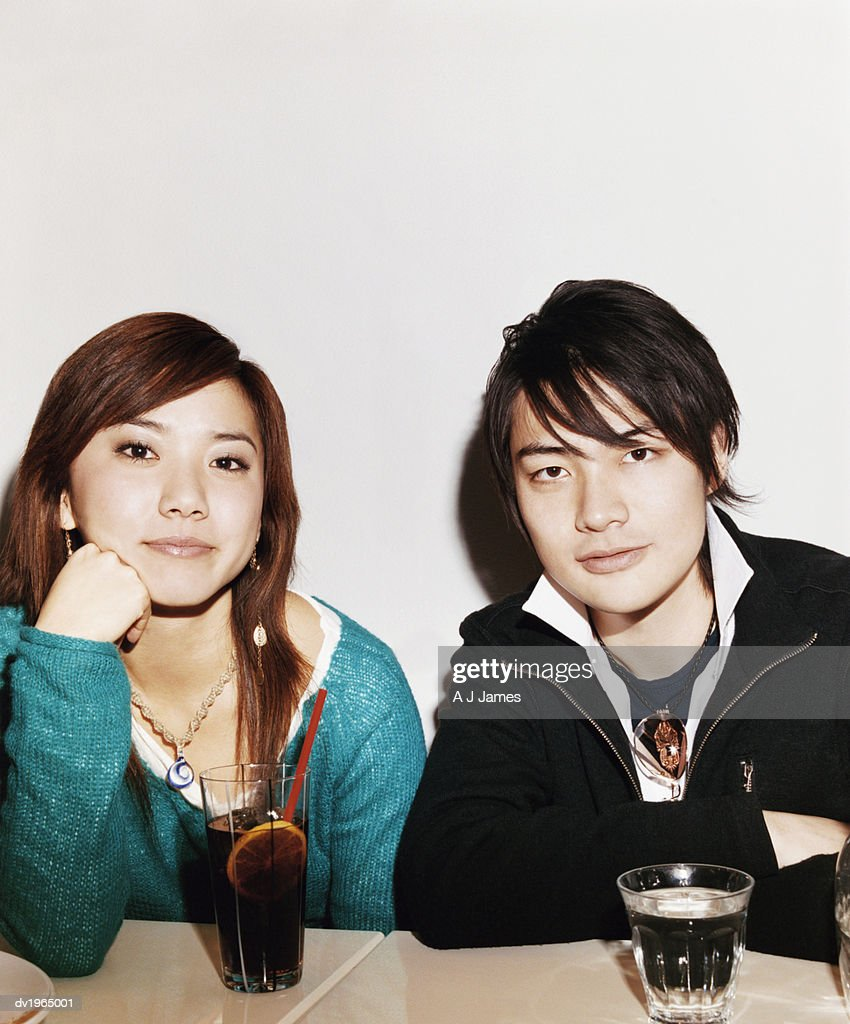 Portrait of a Couple Sitting at a Table With Drinks : Stock Photo