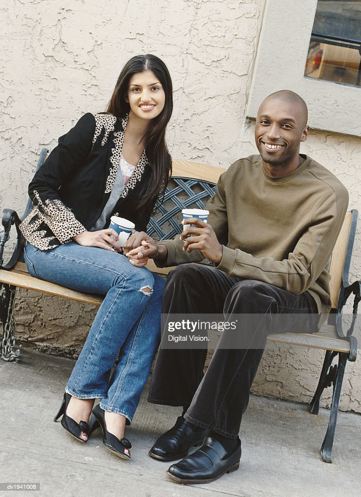 Portrait of a Couple Sitting on a Bench Holding Hands : Stock Photo