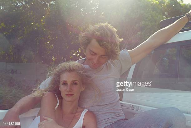 Portrait of a couple sitting on a pick up truck