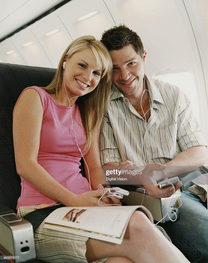 Portrait of a Couple Sitting on a Plane, Holding MP3 Players : Stock Photo