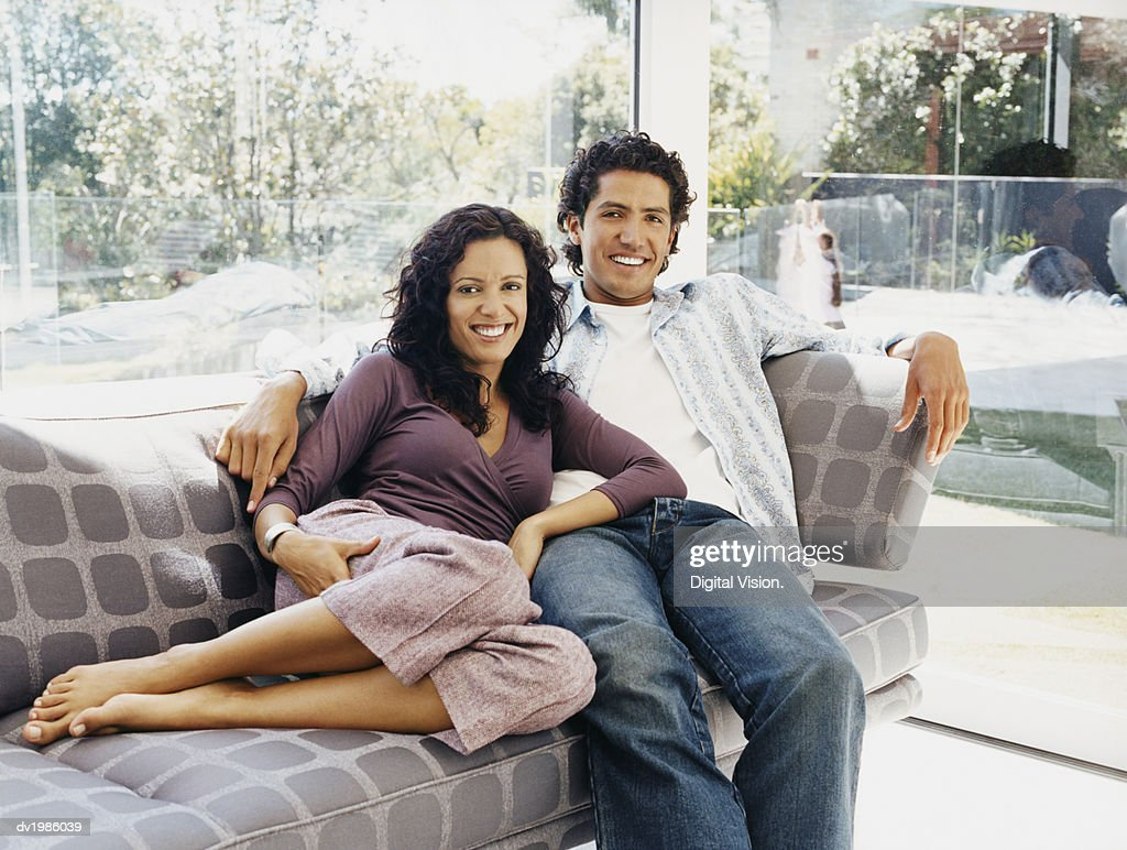Portrait of a Couple Sitting on a Sofa in Their Home : Stock Photo