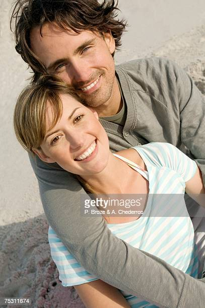 Portrait of a couple smiling on the beach, posing for the camera, outdoors