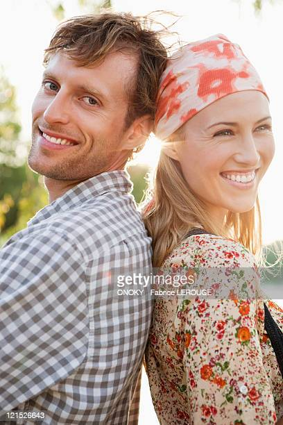 Portrait of a couple standing back to back and smiling