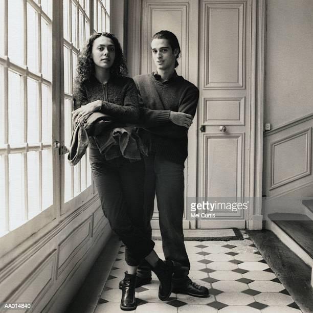 portrait of a couple standing in a stairwell - heteroseksueel koppel stockfoto's en -beelden
