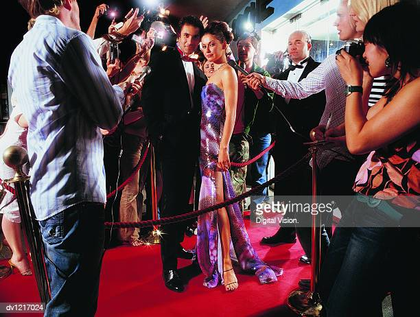 portrait of a couple standing on a red carpet being photographed by paparazzi at night - red carpet event stock-fotos und bilder