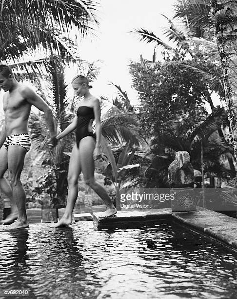 portrait of a couple walking by a swimming pool - young men in speedos stock photos and pictures
