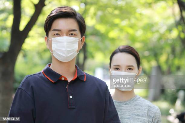 portrait of a couple wearing flu mask - flu mask stock photos and pictures