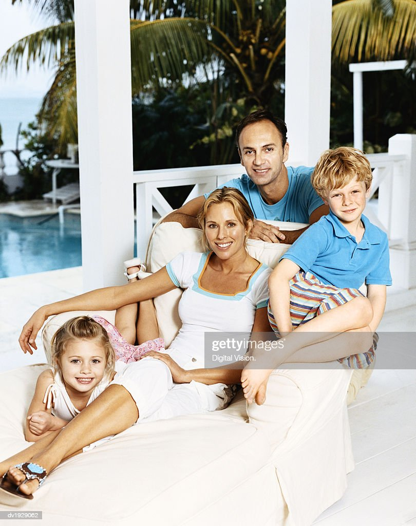 Portrait of a Couple With a Young Son and Daughter Sitting on a Lounger Chair on Their Porch : Stock Photo