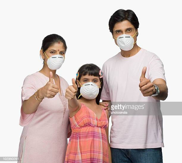 Portrait of a couple with their daughter showing thumbs up sign