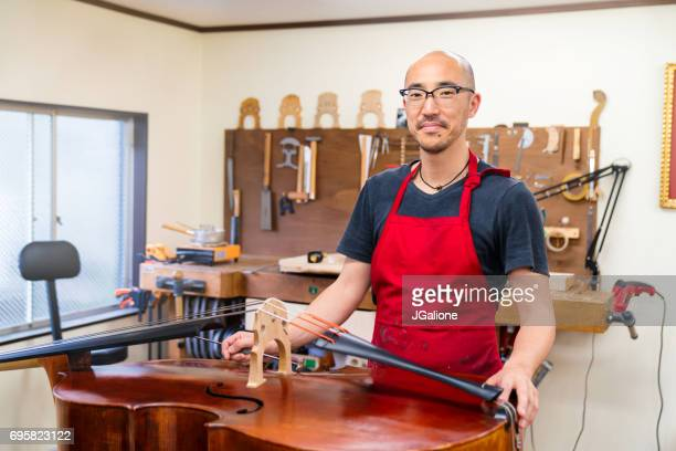 portrait of a craftsman looking into the camera - instrument maker stock photos and pictures
