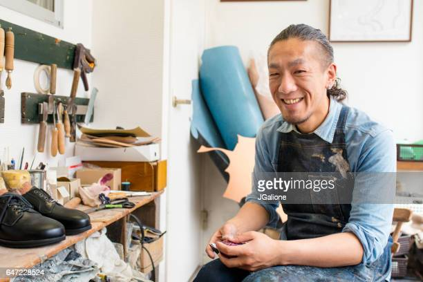portrait of a craftsman repairing a pair of shoes - jgalione stock pictures, royalty-free photos & images