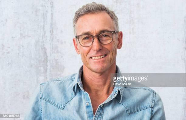 portrait of a creative man wearing glasses. - デニムシャツ ストックフォトと画像