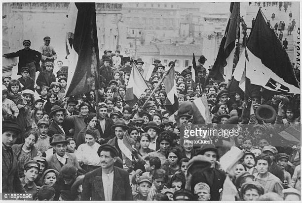 Portrait of a crowd a number of whom wave flags as they celebrate the World War I Armistice Rome Italy December 1918