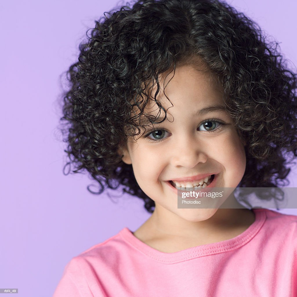 portrait of a cute african american girl in a pink shirt smiles brightly into the camera : Stockfoto