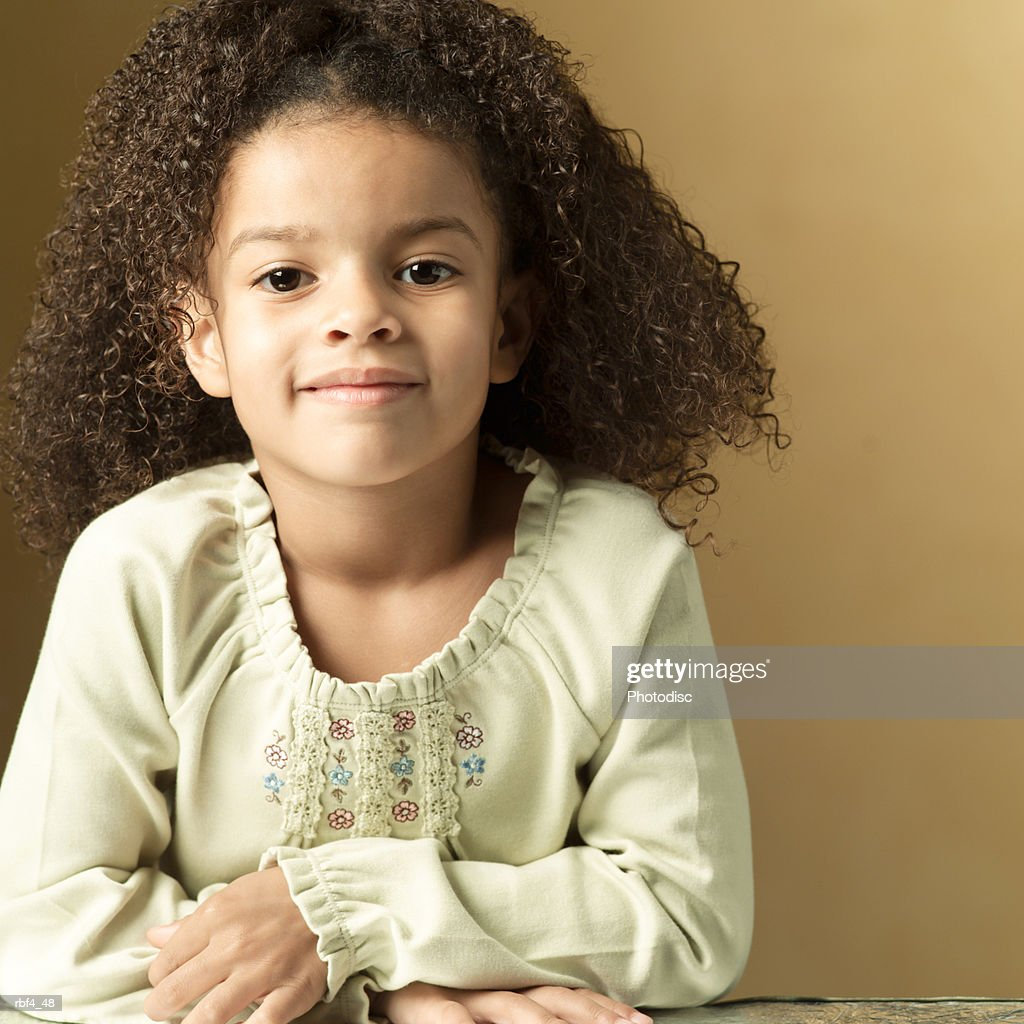 portrait of a cute african american girl in a tan sweater folds her arms and smiles slightly : Stockfoto