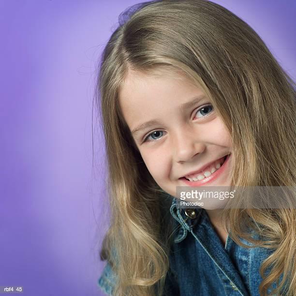 portrait of a cute blonde caucasian girl in a blue denim jacket with a purple background as she smiles