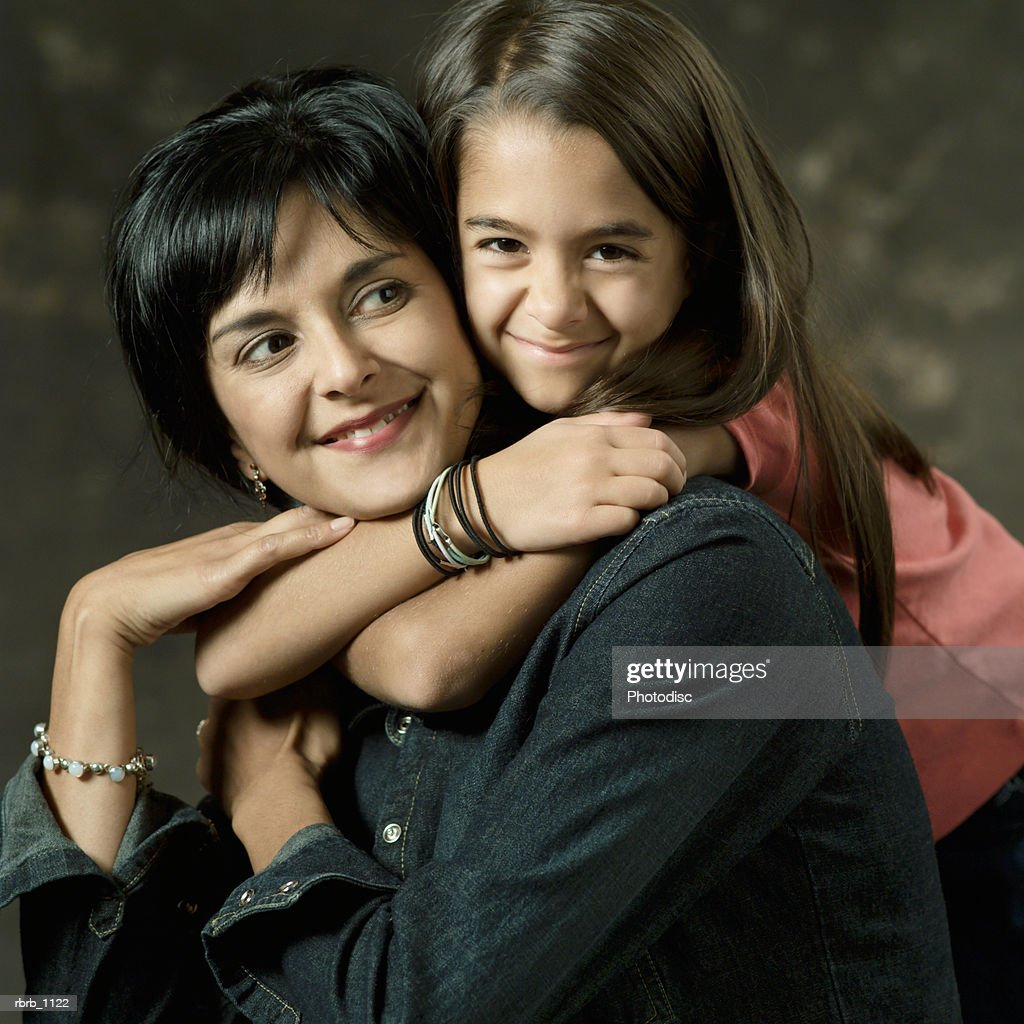 portrait of a cute ethnic girl as she hugs her mother from behind : Stockfoto
