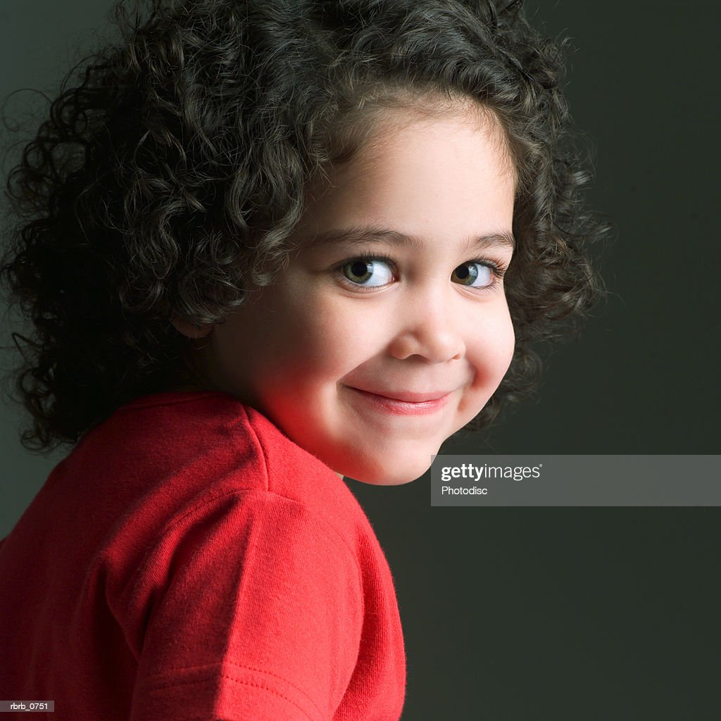 portrait of a cute little african american girl in na red shirt as she turns and smiles : Stockfoto
