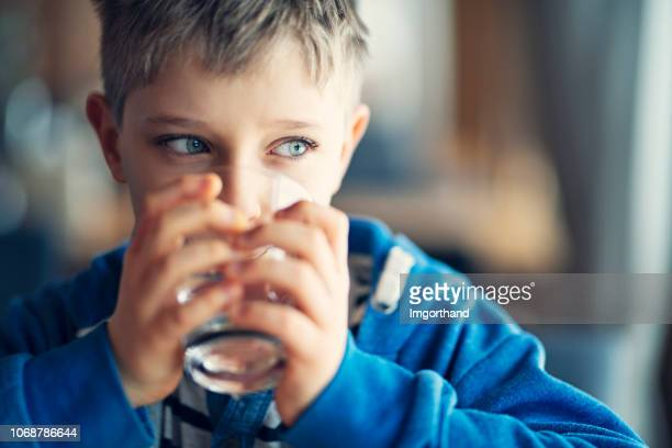 portrait of a cute little boy drinking a glass of water - acqua foto e immagini stock