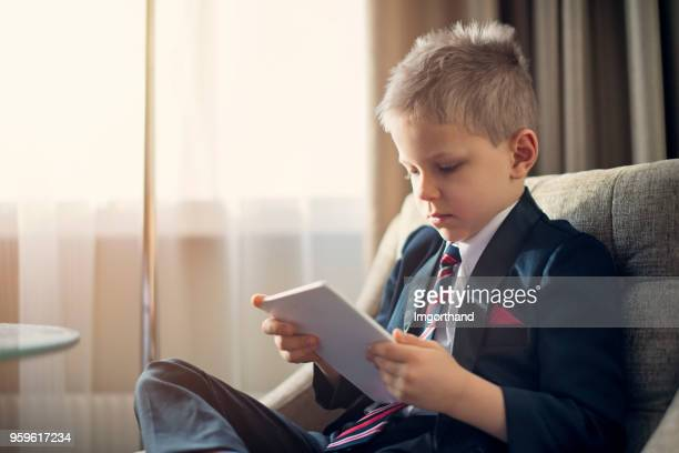 portrait of a cute little business man checking tablet - adult imitation stock pictures, royalty-free photos & images