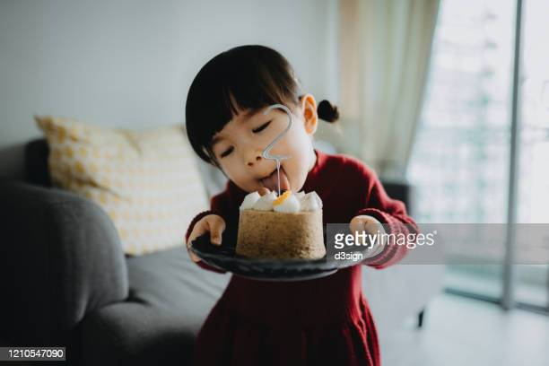 portrait of a cute little girl holding a birthday cake celebrating her two years old birthday and sticks out her tongue attempting to lick the cake - 2 3 years stock pictures, royalty-free photos & images