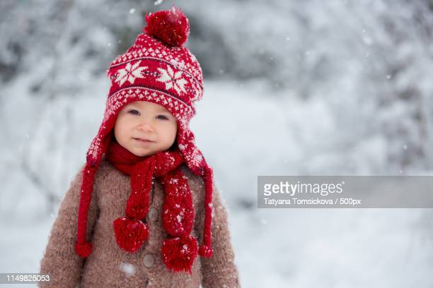 Portrait Of A Cute Toddler Baby Dressed In A Brown Hand Knitted