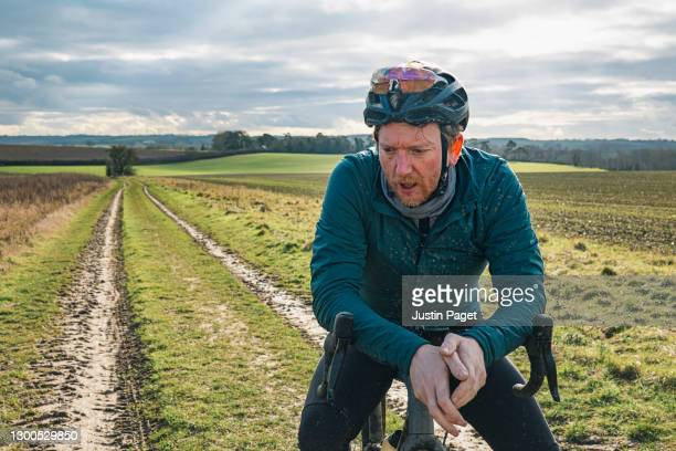 portrait of a cyclist on rural track - tired stock pictures, royalty-free photos & images