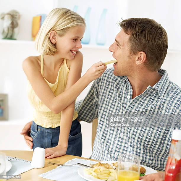 portrait of a daughter feeding her father - french fries stock pictures, royalty-free photos & images