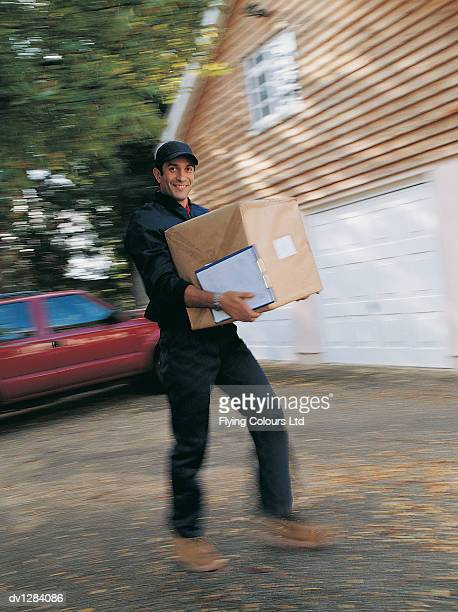 Portrait of a Delivery Man Holding a Parcel Walking Up a Driveway to a House