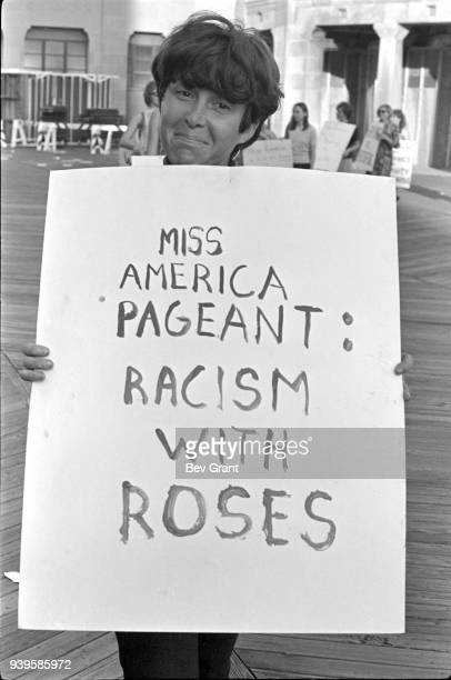 Portrait of a demonstrator as she holds a poster that reads 'Miss America Pageant: Racism with Roses' as she poses on the Atlantic City Boardwalk...