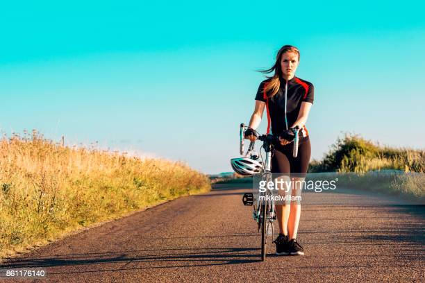 portrait of a determined female athlete and her racing bicycle - puncturing stock pictures, royalty-free photos & images