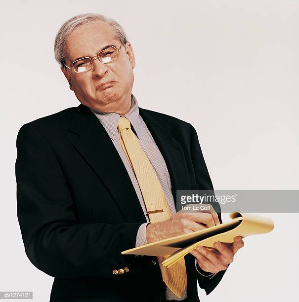 Portrait of a Displeased Mature Businessman Holding a Notepad and Pen