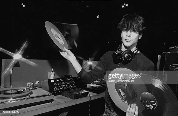 Portrait of a DJ as he poses with several records in the booth at the Ritz New York New York mid to late twentieth century