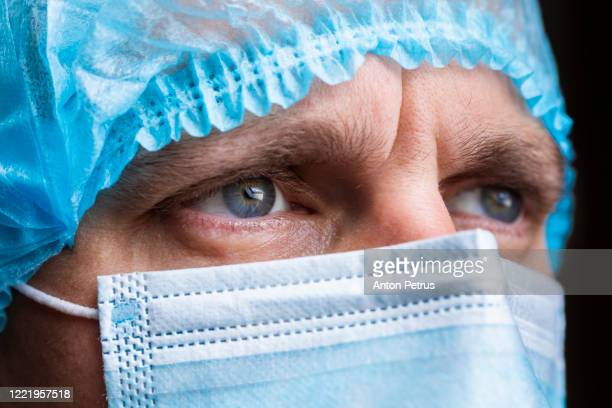 portrait of a doctor in a medical mask and a protective cap. - coronavirus doctor stock pictures, royalty-free photos & images