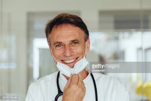 portrait of a doctor, removing surgical mask, smiling - absence stock pictures, royalty-free photos & images