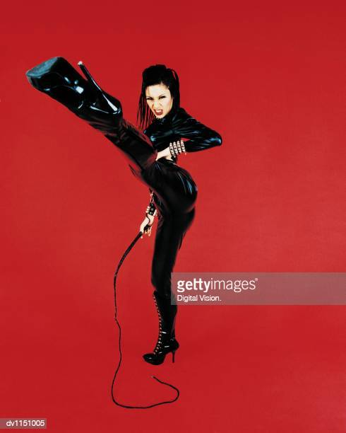 portrait of a dominatrix holding a whip and standing on one leg - dominatrice foto e immagini stock