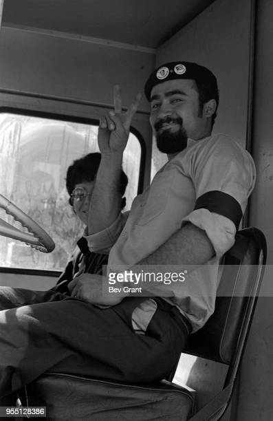 Portrait of a driver with a black armband and a beret as he gives a 'V' sign seated behind the wheel of his truck outside the Time Life Building...