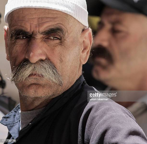 CONTENT] A portrait of a Druze man with the typical mustache and a skullcap gazing to the side