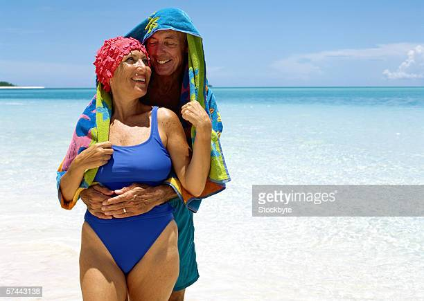 portrait of a elderly man hugging his wife at the beach