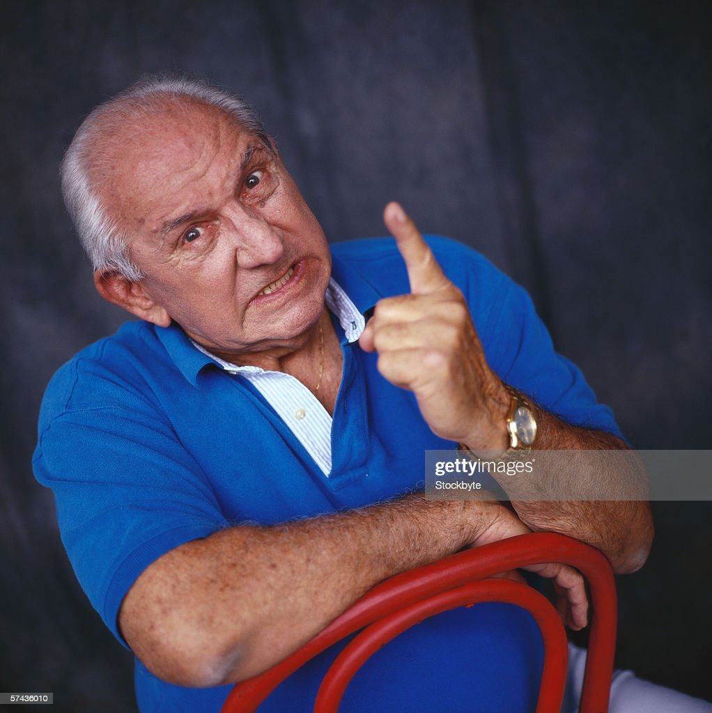 portrait of a elderly man pointing out his finger in anger : Stock Photo