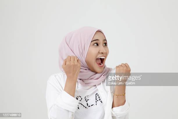 portrait of a exciting young woman against white background - 宗教的なベール ストックフォトと画像