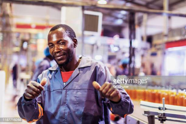 portrait of a factory worker gesturing thumbs up - zambia stock pictures, royalty-free photos & images