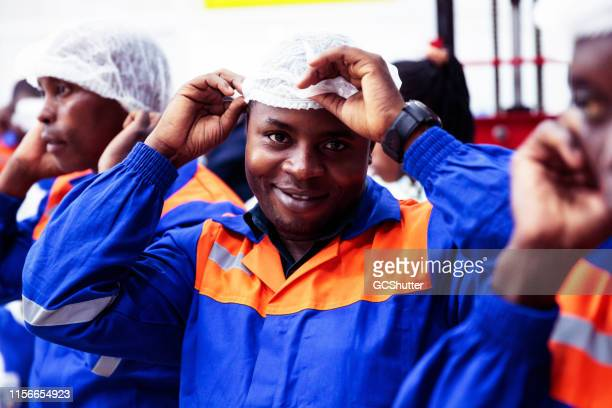 portrait of a factory worker standing among his coworkers - africa - may day international workers day stock pictures, royalty-free photos & images