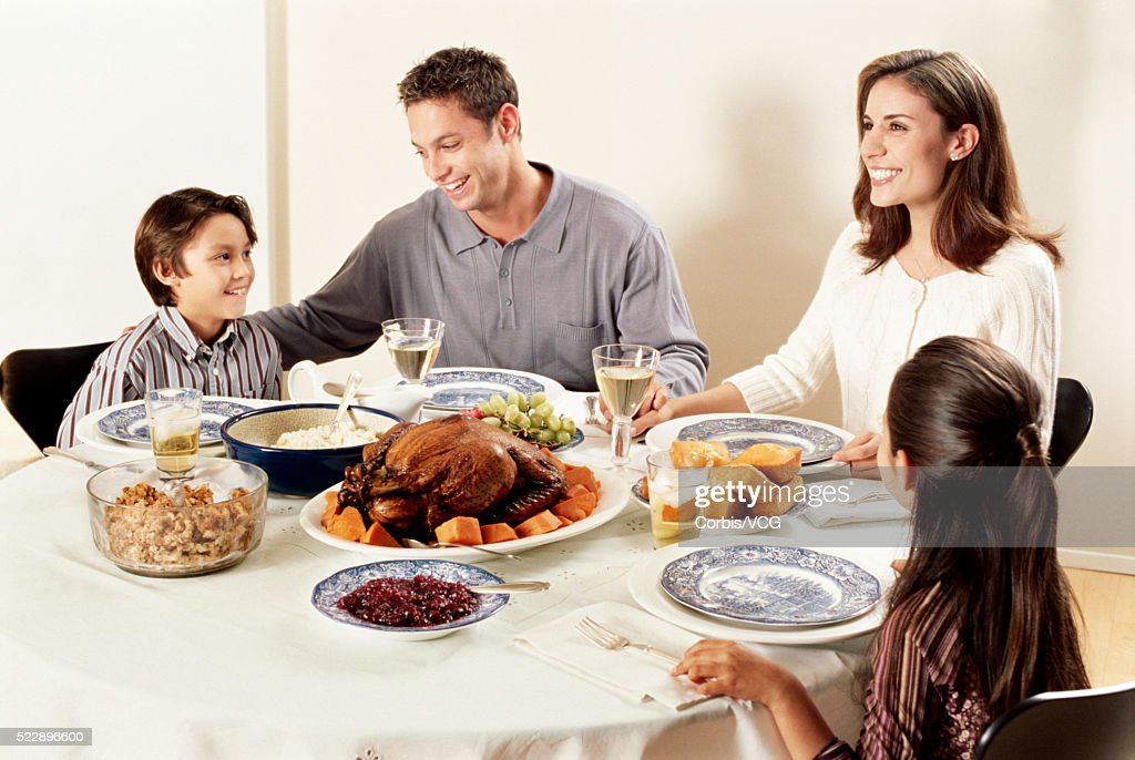 Portrait Of A Family Eating Thanksgiving Dinner Together Stock Photo