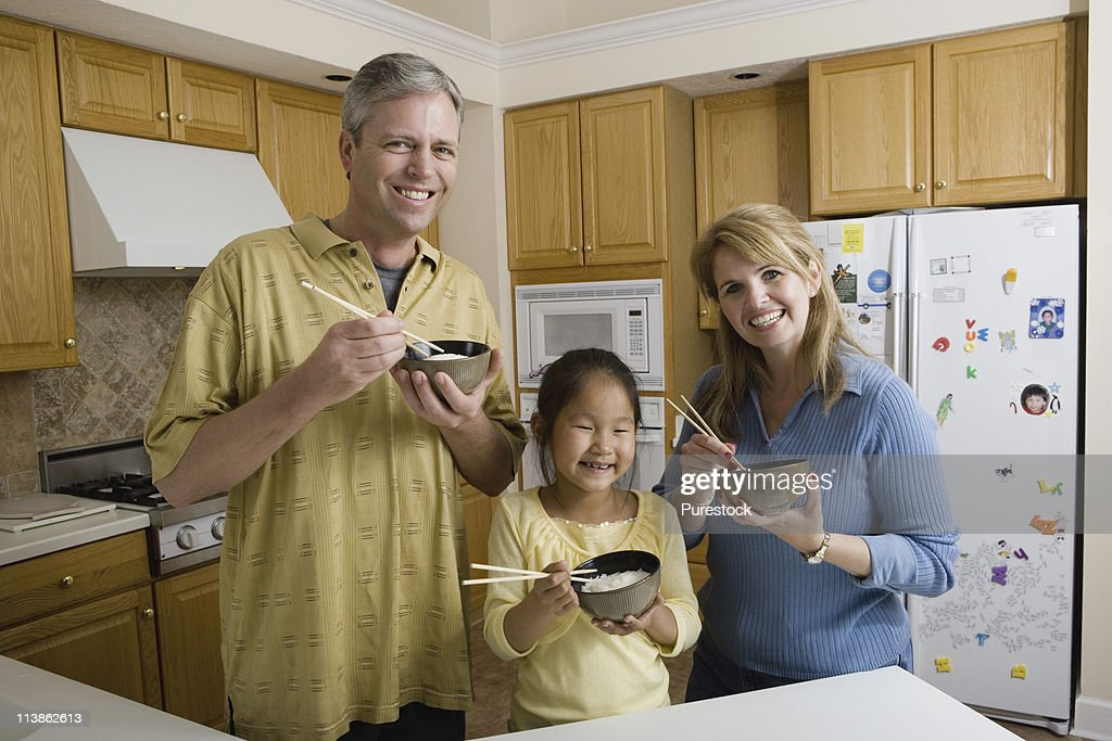 Portrait of a family in kitchen holding bowls of rice and chopsticks : Stock Photo