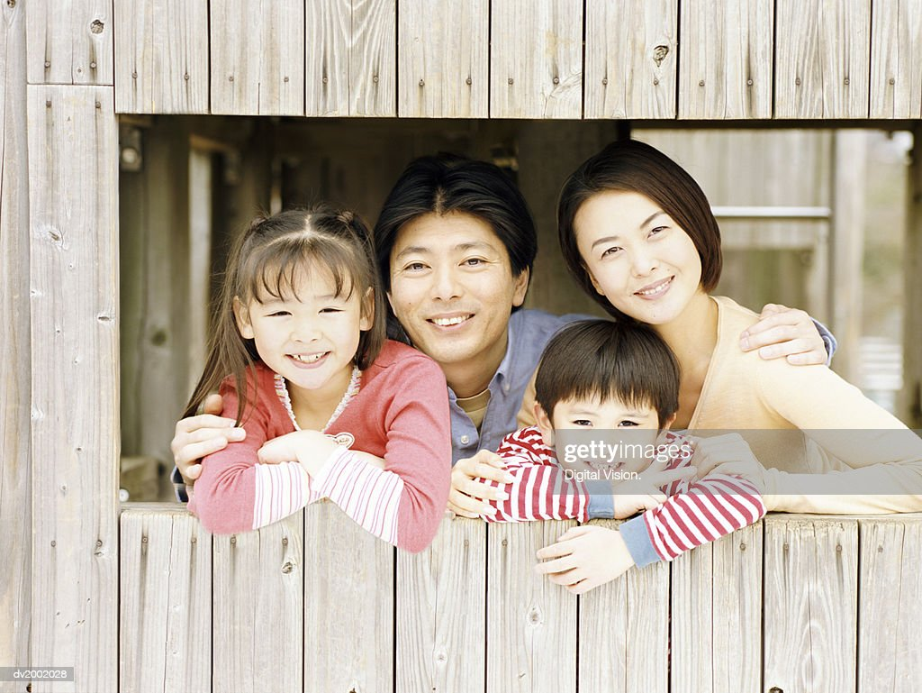 Portrait of a Family Looking Through a Hole in a Tree House : Stock Photo