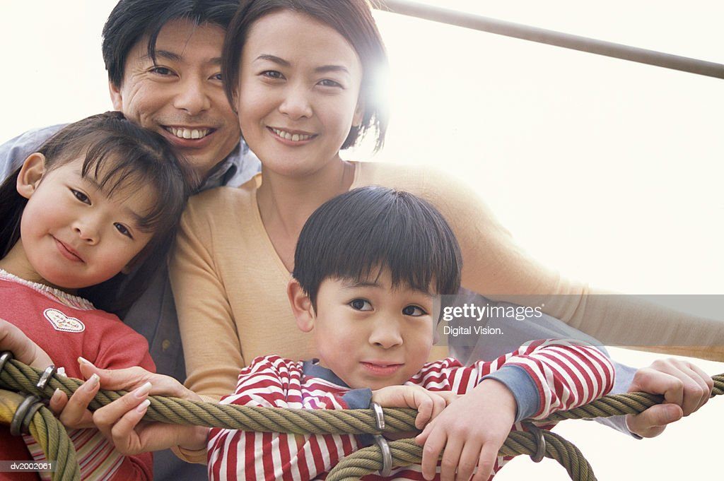 Portrait of a Family of Four on a Climbing Frame : Stock Photo